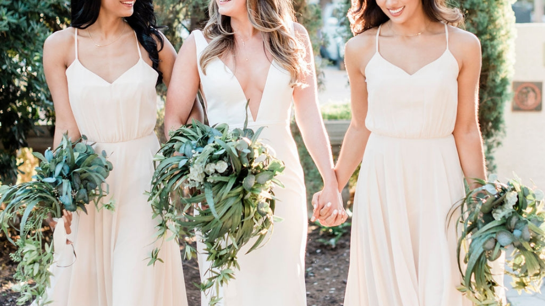lyra wedding dress revelry bridal with deep neckline and flattering waist next to bridesmaids holding greenery bouquets