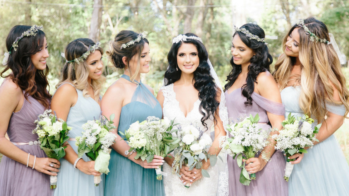 Mix and match violet and blue tulle bridesmaids pose with bride in bohemian forest.