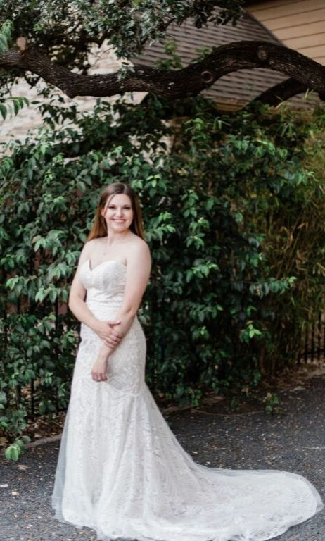 Megan in decklyn bridal gown art deco wedding dress smiling and posiing full body shot in front of greenery