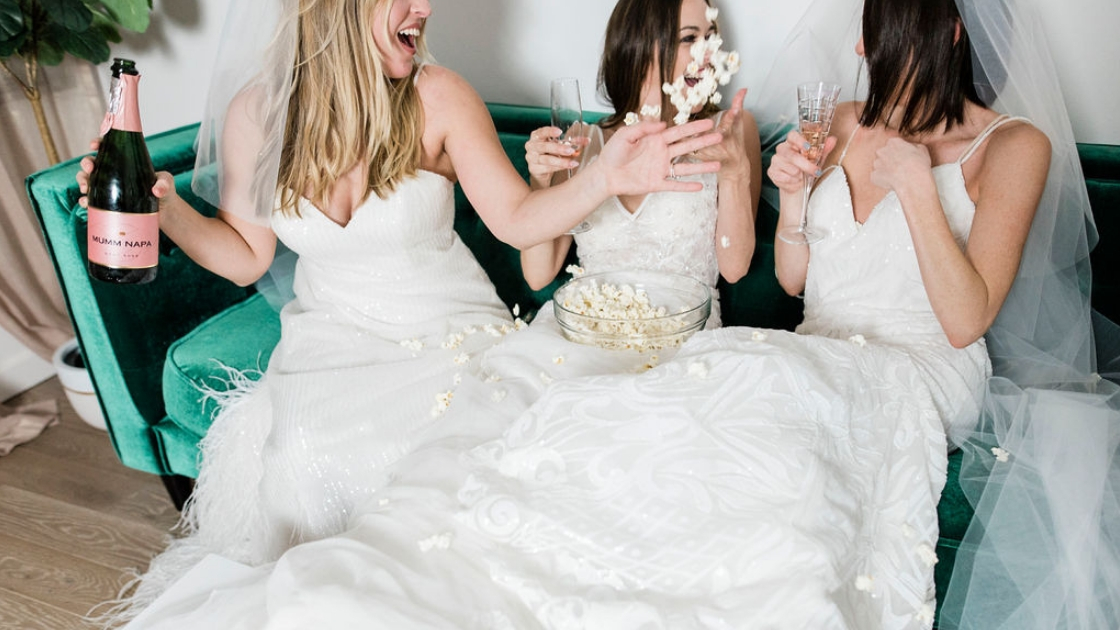 Michelle and besties laugh and smile on couch wearing wedding dresses eating popcorn and drinking champagne