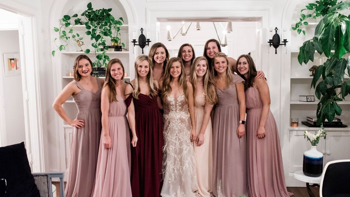 blonde bride-to-be and bridesmaids in pink and blush chiffon dresses smile and pose at dallas texas try on party revelry