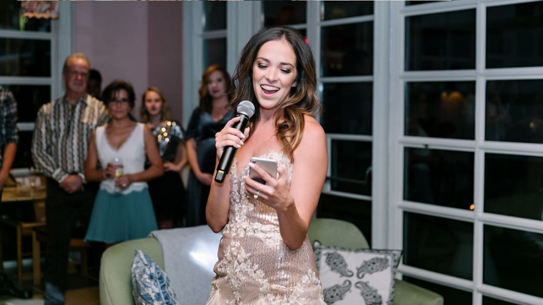 Michelle revelry founder holding phone and reading speech in rose gold sequin cocktail gown with mic as team watches and celebrates accomplishments