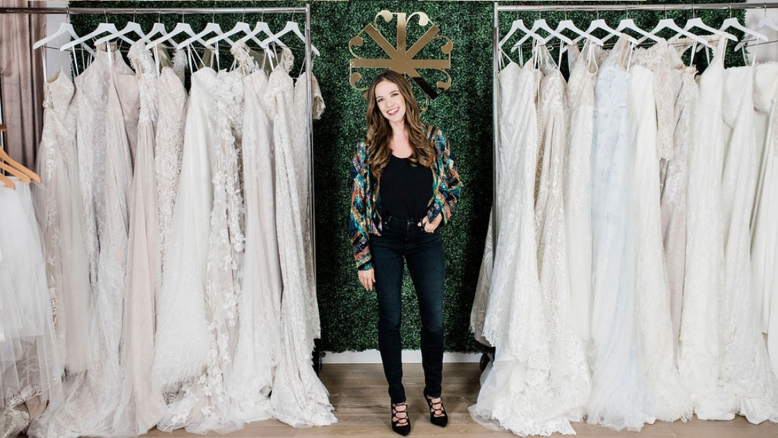 Michelle Revelry Founder Pose in front of wedding dresses green wall austin
