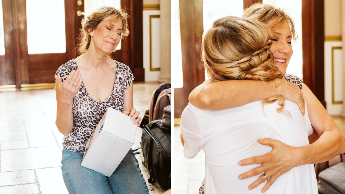 Mother of the bride hugs bride of wedding day with wedding present