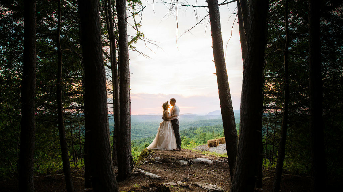 wooded clearing with bride and groom looking into the Maine sunset for first look photos.