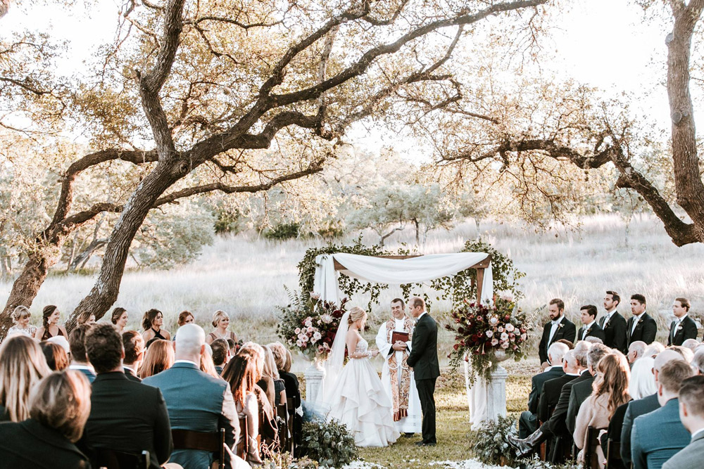 Kathryn and Mitchell Standing together in front of the floral and fabric draped alter under large Texas oak trees at dusk.