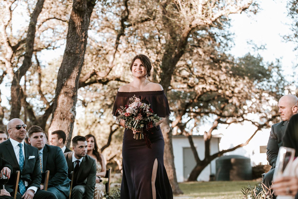 Abigail Off the shoulder boho bridesmaid dress worn while walking down the aisle with moody winter botanicals as bridesmaid bouquet.