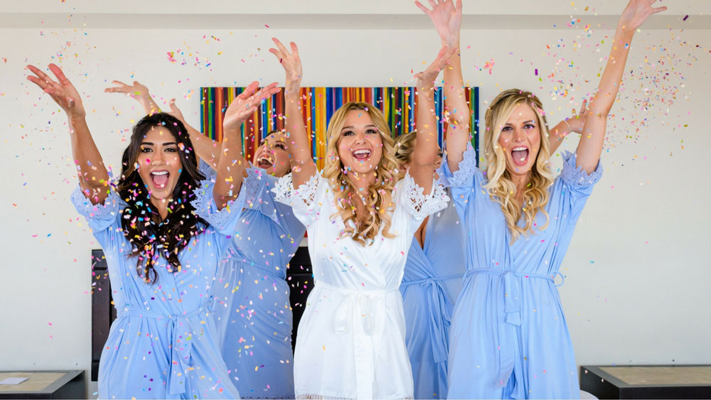 Bridesmaids throwing confetti in the air while getting ready in beautiful blue robes.