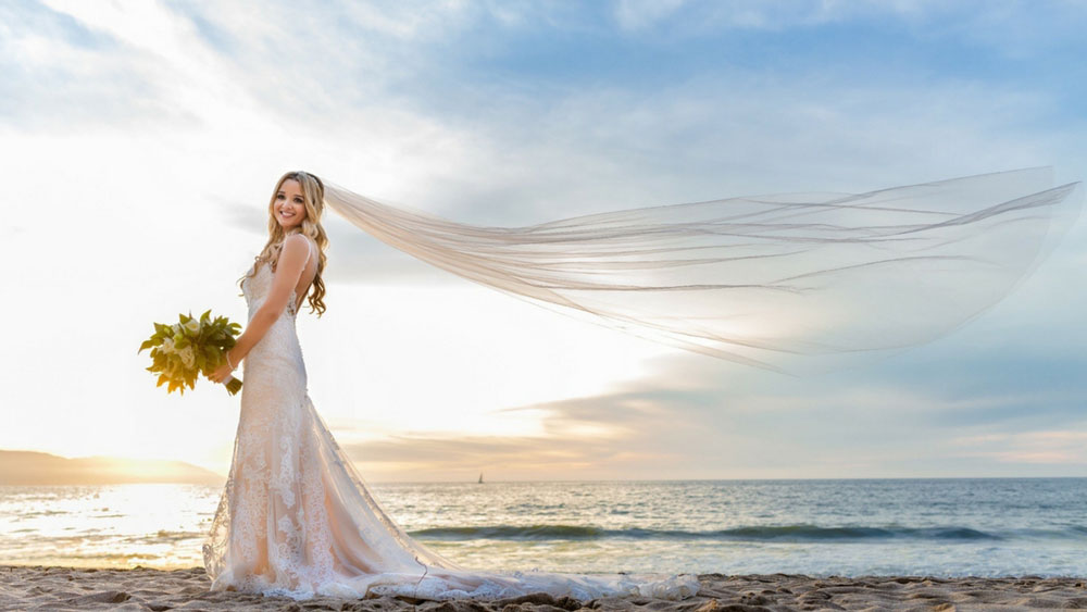 bride on beach with long veil flowing in the wind.