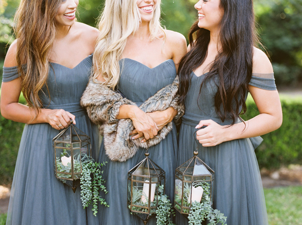three bridesmaids pose together in eucalyptus tulle convertible dresses. Bridesmaids hold candle filled lanterns instead of bouquets. Center bridesmaid with fur for winter wedding vibes.