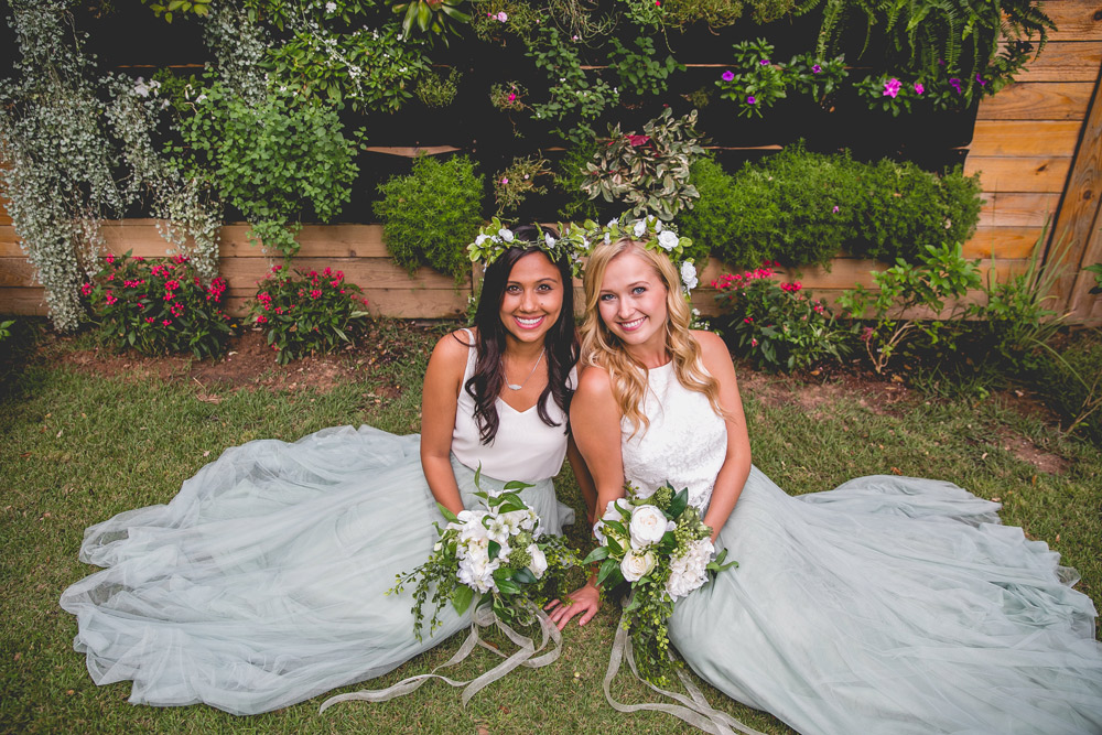 lace tops and tulle skirts with flower crowns on bridesmaids posing together on while sitting on the ground. The tulle skirts flow in the breeze next to bright white bouquets.