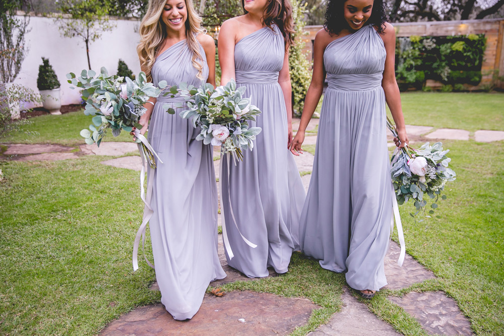bridesmaids walking together in grey chiffon holding eucalyptus bouquets.