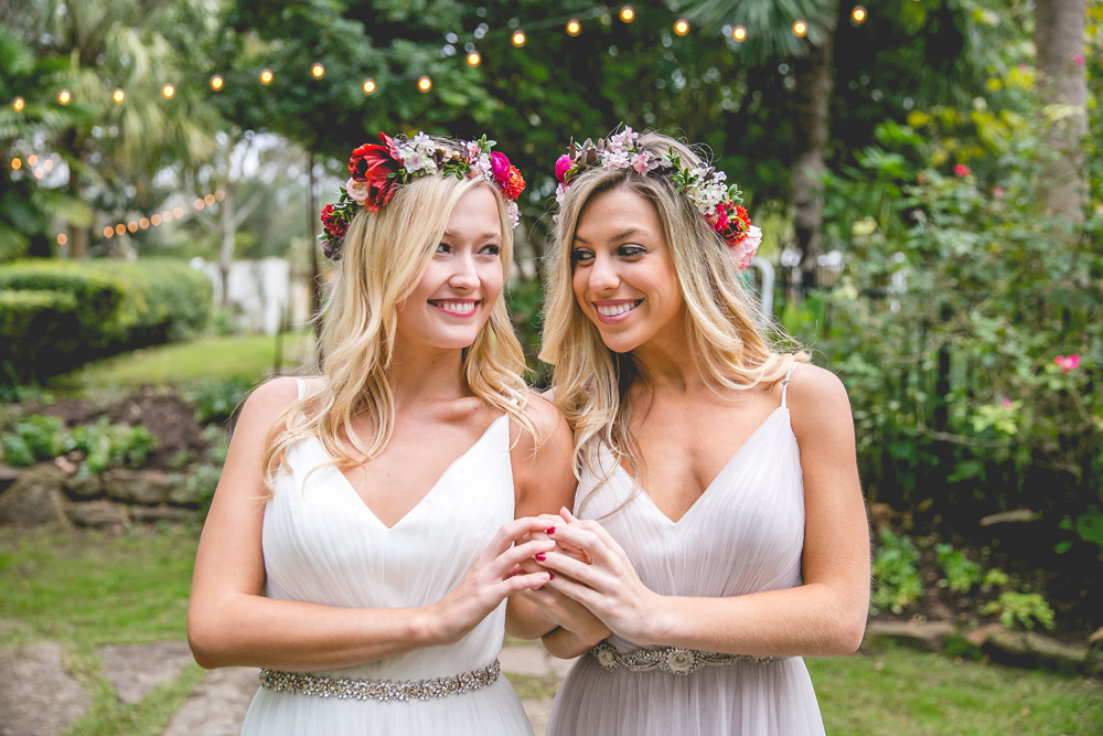 bride and bridesmaid pose together making heart shape with hands in tulle peneleope dresses under twinkle lights in luscious garden venue.