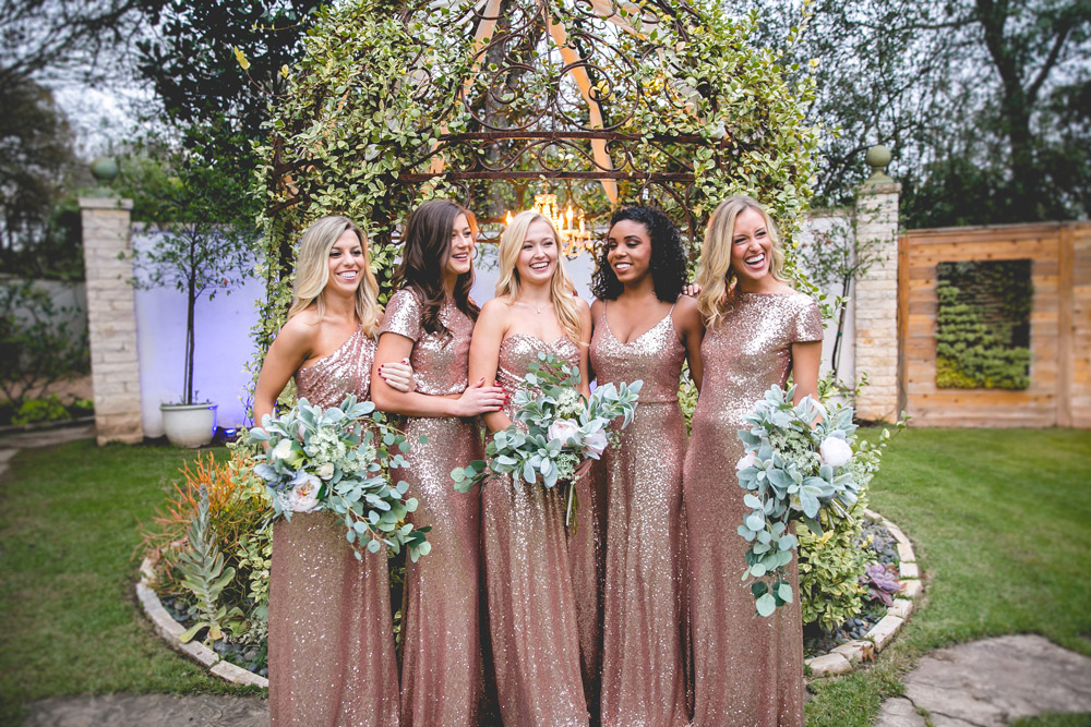 bridesmaids poses together in rose gold sequin and eucalyptus bouquets.
