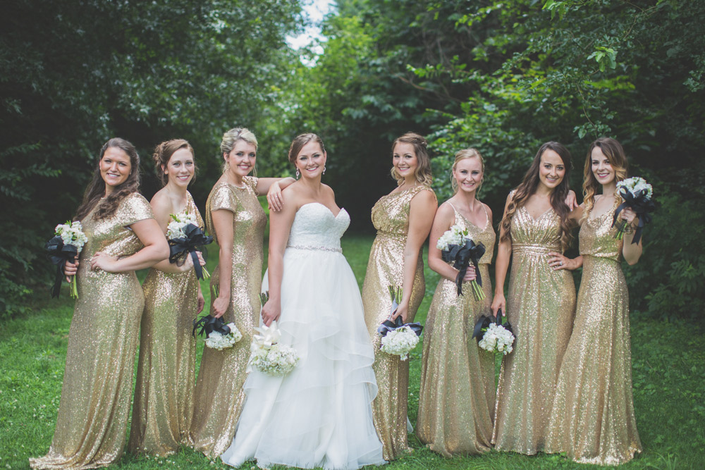 real revelry wedding showing the full range of revelry sequin bridesmaid gowns in gold sequins with bride in tulle in the center.