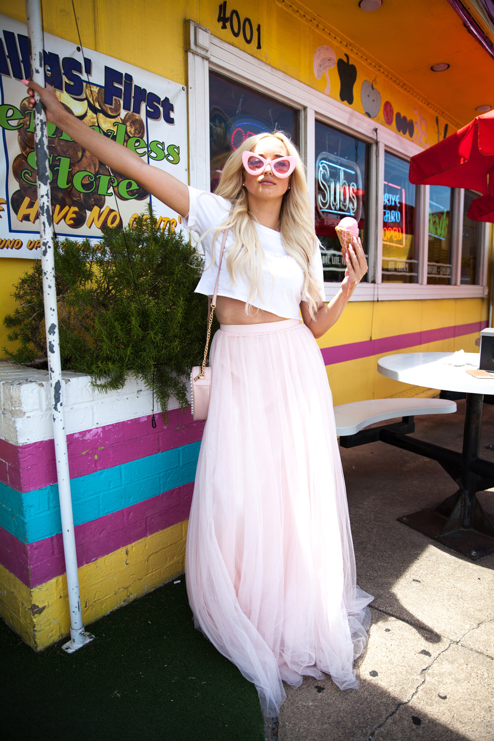 Bridesmaid wears tulle skirt again outside cute ice cream shop. Dresses down pink tulle skirt with white sneakers, cropped tee , and vintage inspired cat eye sunglasses.