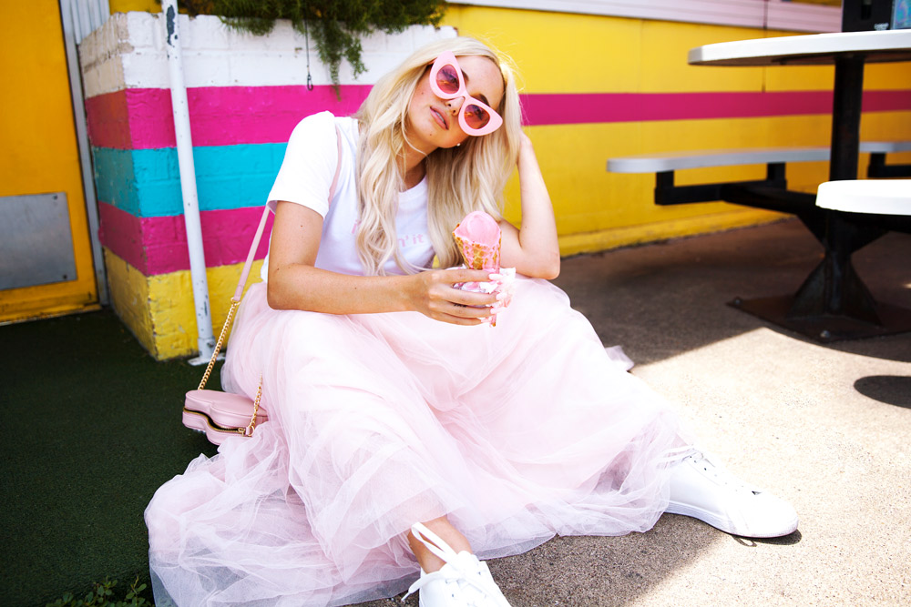 Vintage inspired shoot featuring pink cat eye sunglasses , cropped cap sleeve t shirt, and revelry pink tulle skirt. Model wears a pink heart shaped purse, white sneakers, and holds an ice cream cone.