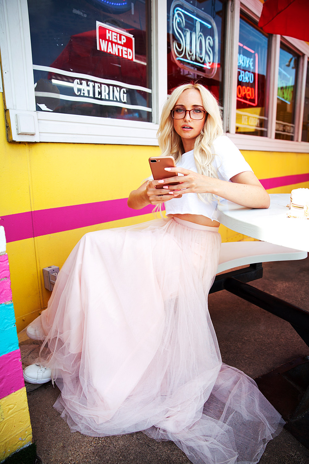 Rachel Page wears Tulle skirt & tshirt combo while texting outside a cute vintage restaurant.