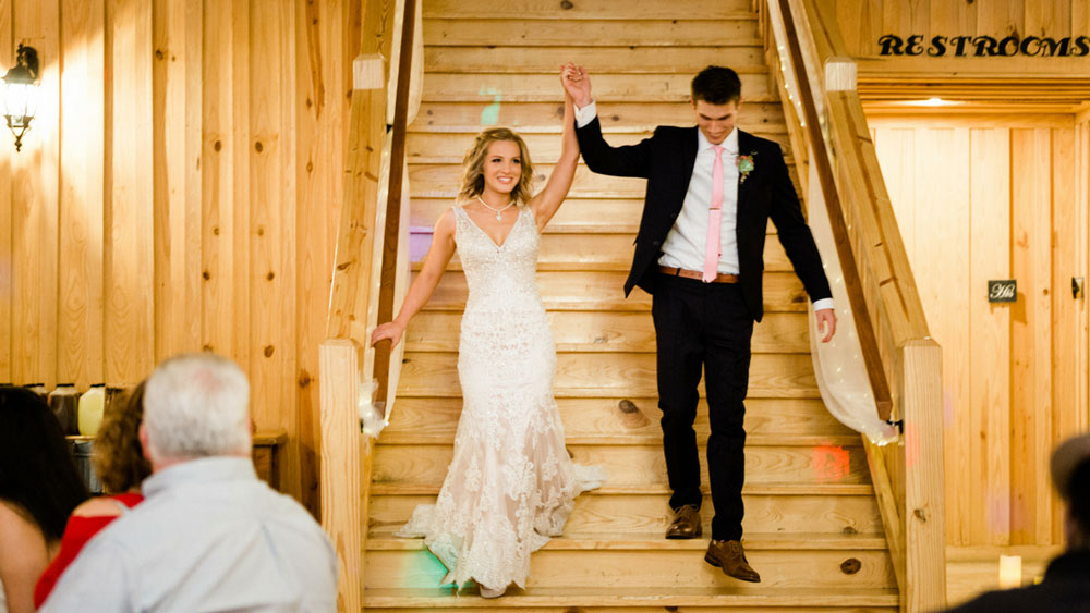 bride and groom walk down the wooden stairs to make a grand entrance to their reception