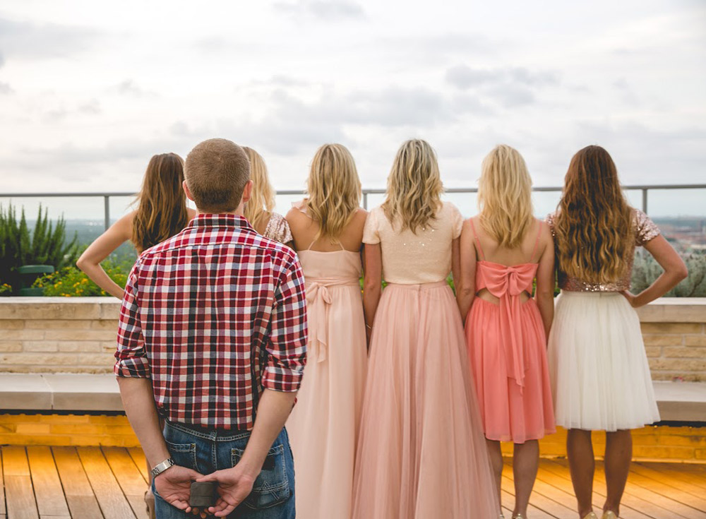 The groom stands behind the soon to be bride and her friends. waiting to surprise her with the ring!