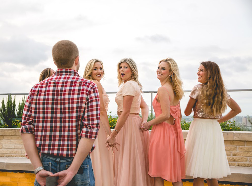 Bride to be spots her future husband with a shocked expression on her face and her best friends grinning ear to ear in revelry bridesmaid looks.