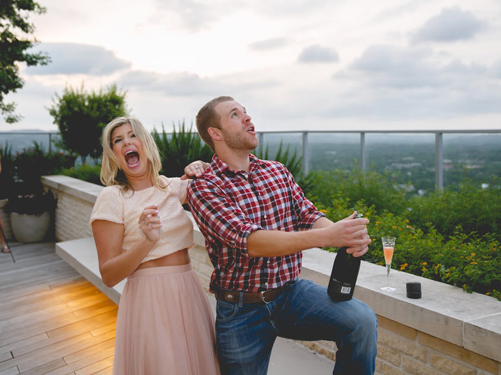 The newly engaged couple pops a bottle of champagne on top of Austin rooftop. Bride to be wears pink tulle skirt and barely blush sequin tshirt top.