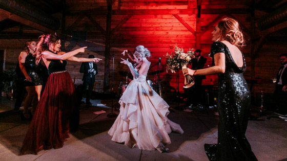 bride dances with Revelry bridesmaids in tulle and sequins