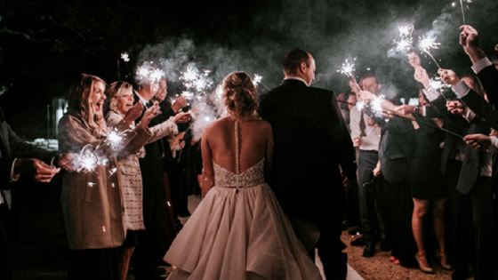 Bride and groom exiting under sparkler tunnel