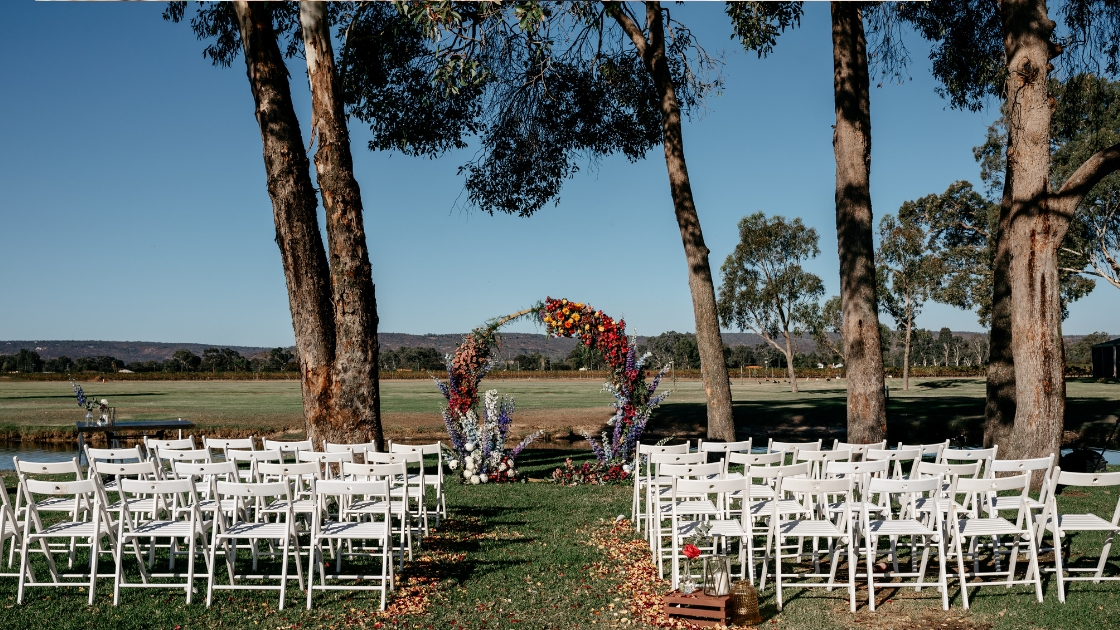 Outdoor fall ceremony with floral alter white chairs oak trees by lake