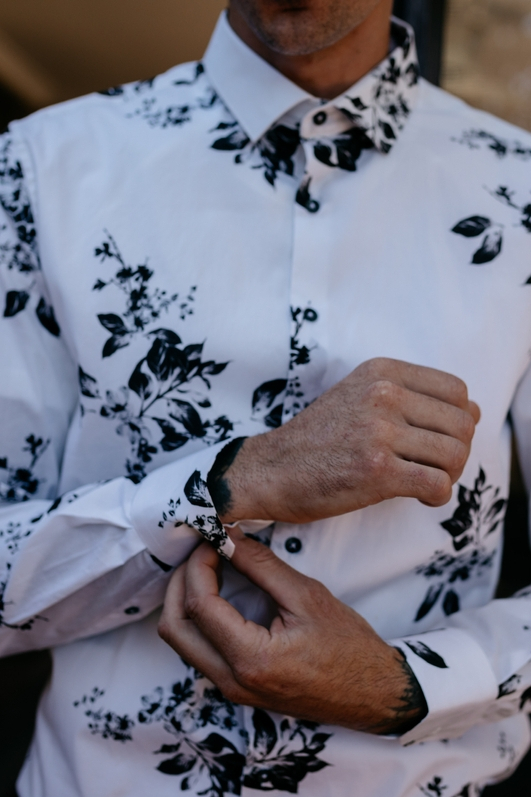 groom in white shirt with black printed flowers close up putting cufflinks on on wedding day tattooed groom detail shot