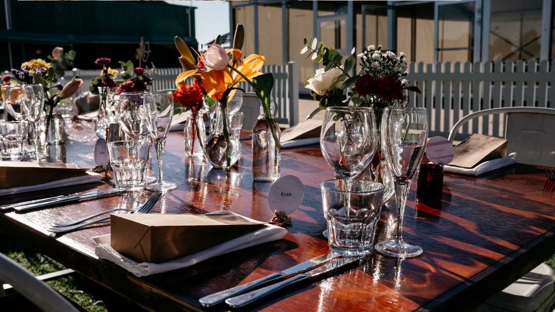 Place setting of outdoor boho wedding with flowers in cases and wine glasses on table boho ceremony and reception