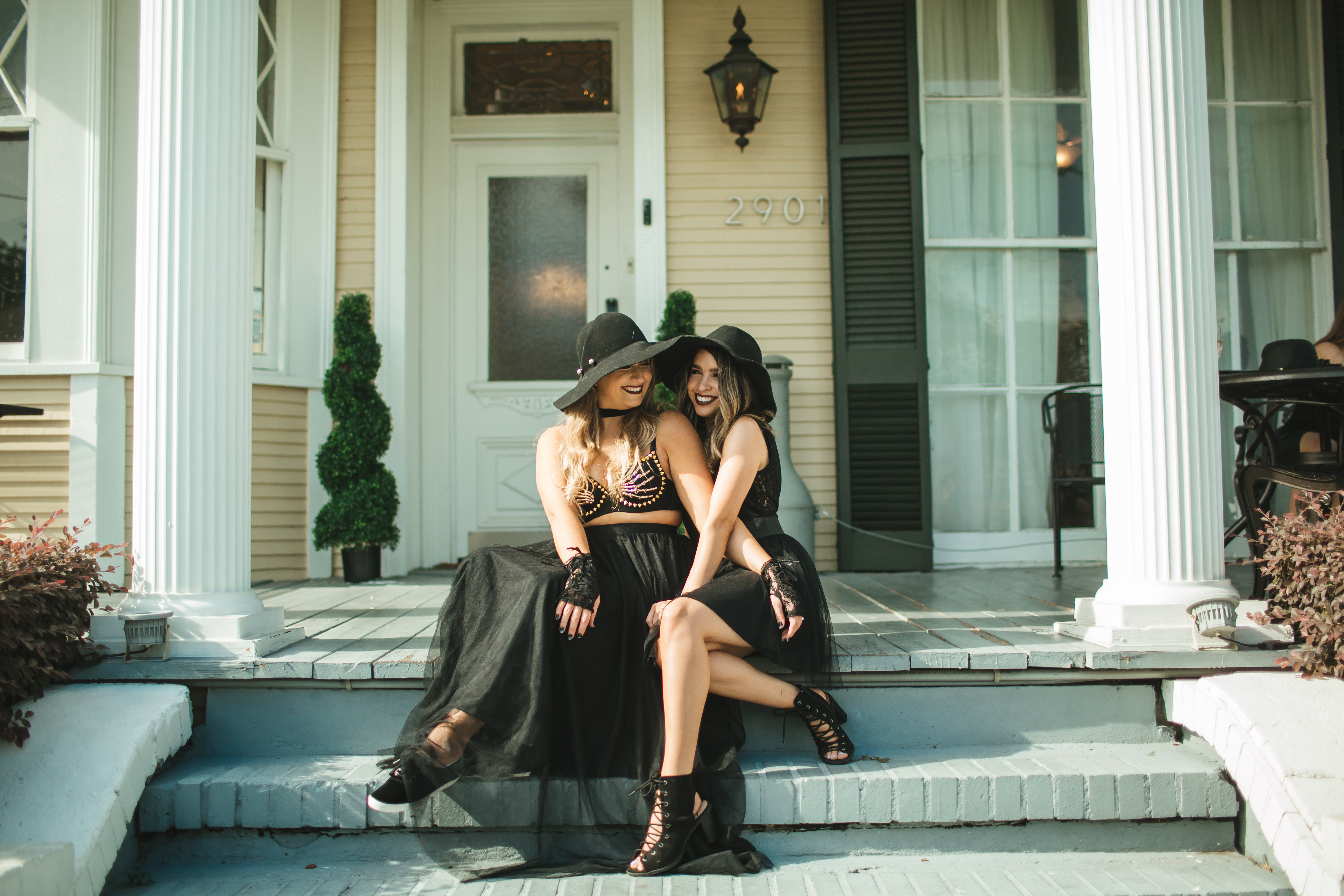 Bride Rachel and her bridesmaid cristina posing in front of their haunted mansion in New Orleans.