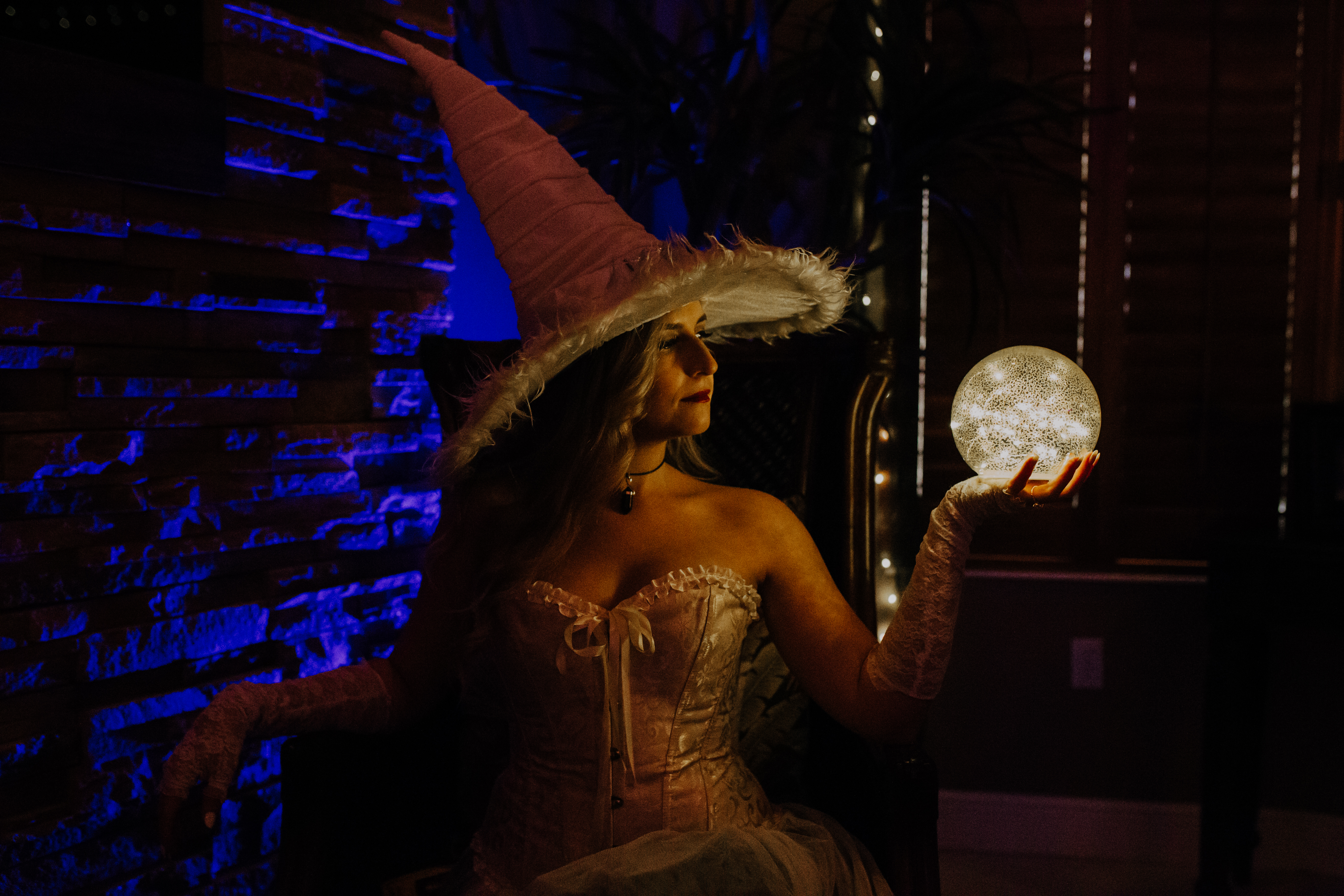 White witch costume poses in moody lighting with crystal ball orb