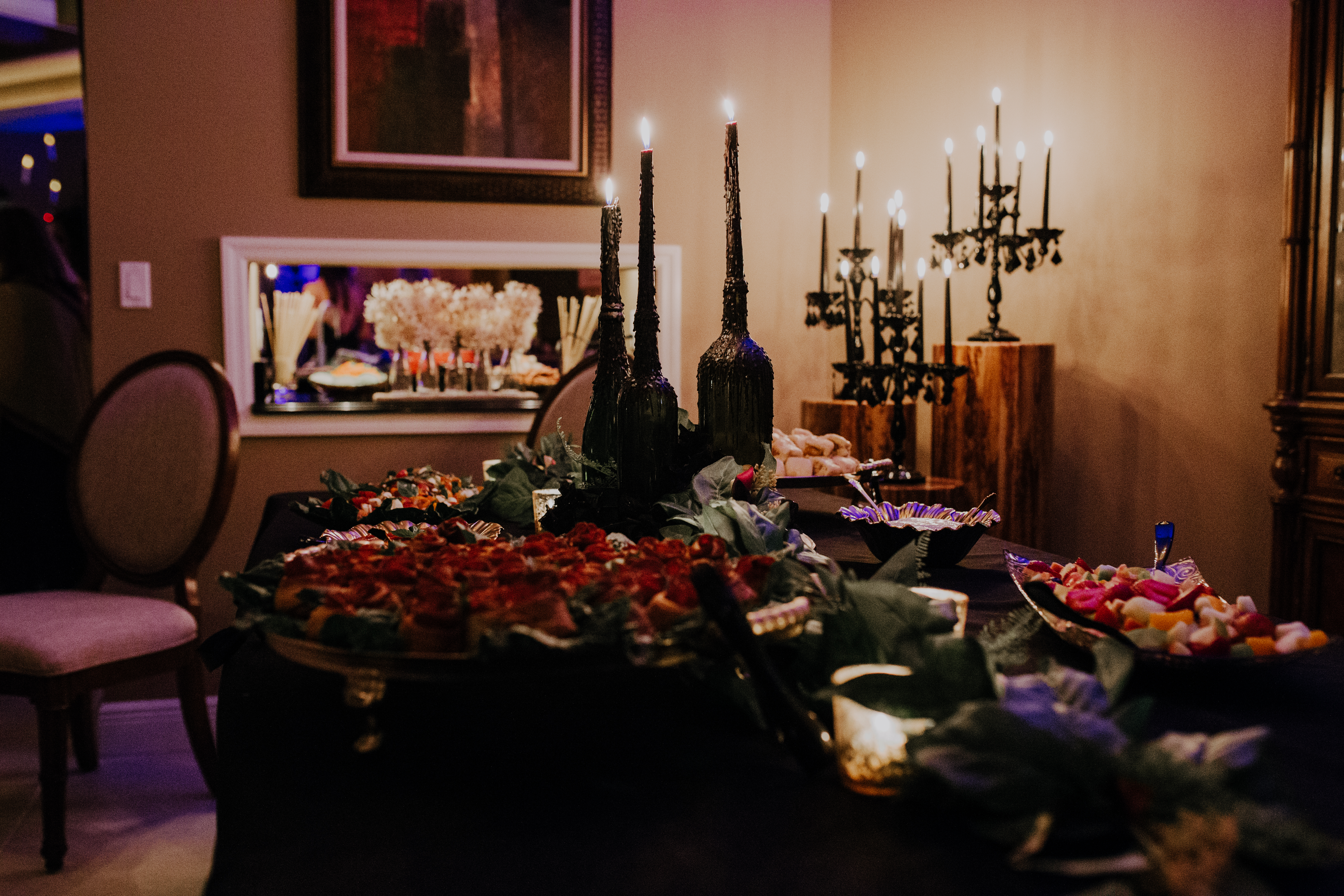 A gothic display of food and candles create a moody fall bridal shower