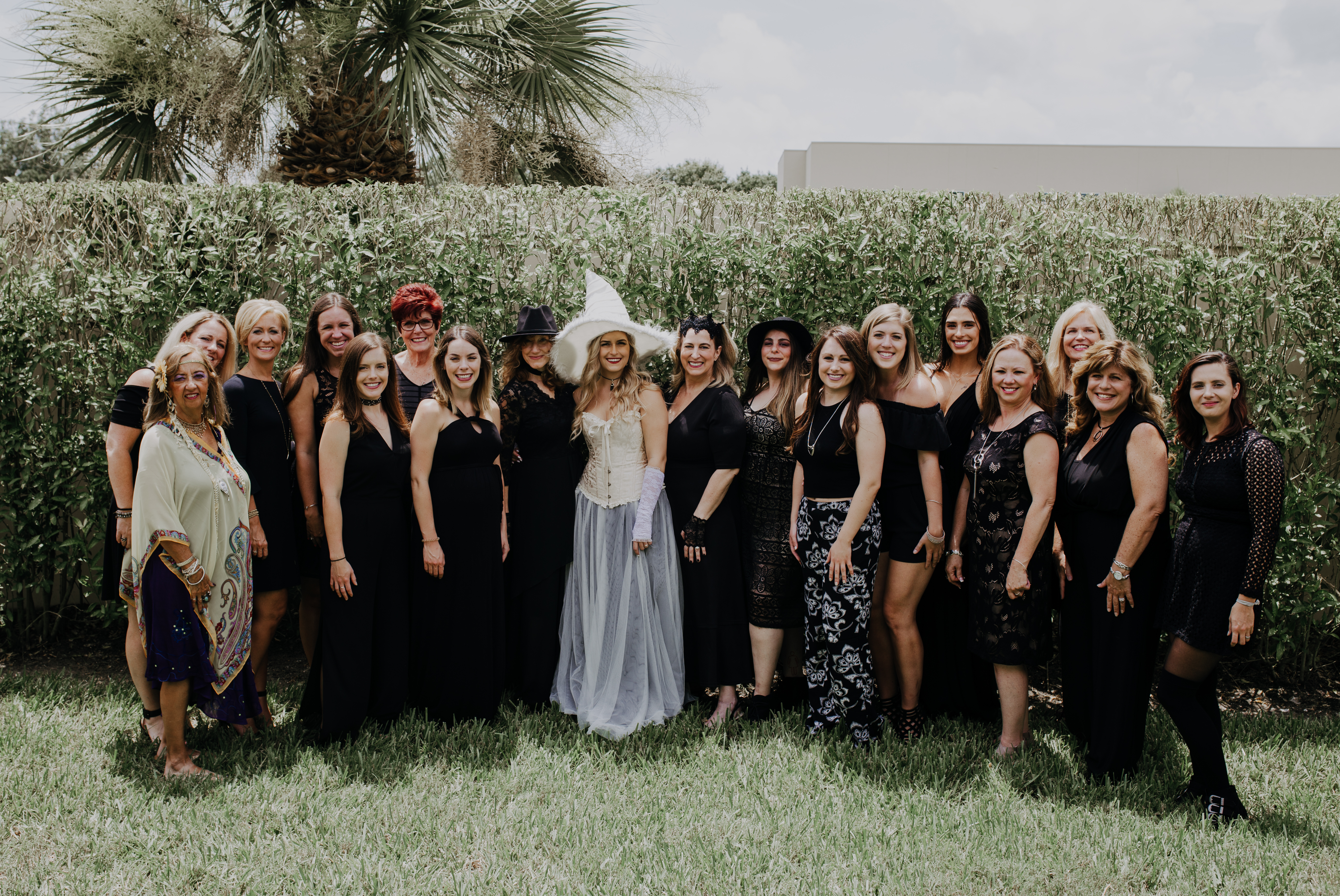 bride with poses outside with friends and family all in black at her halloween coven harry potter magical bridal shower party