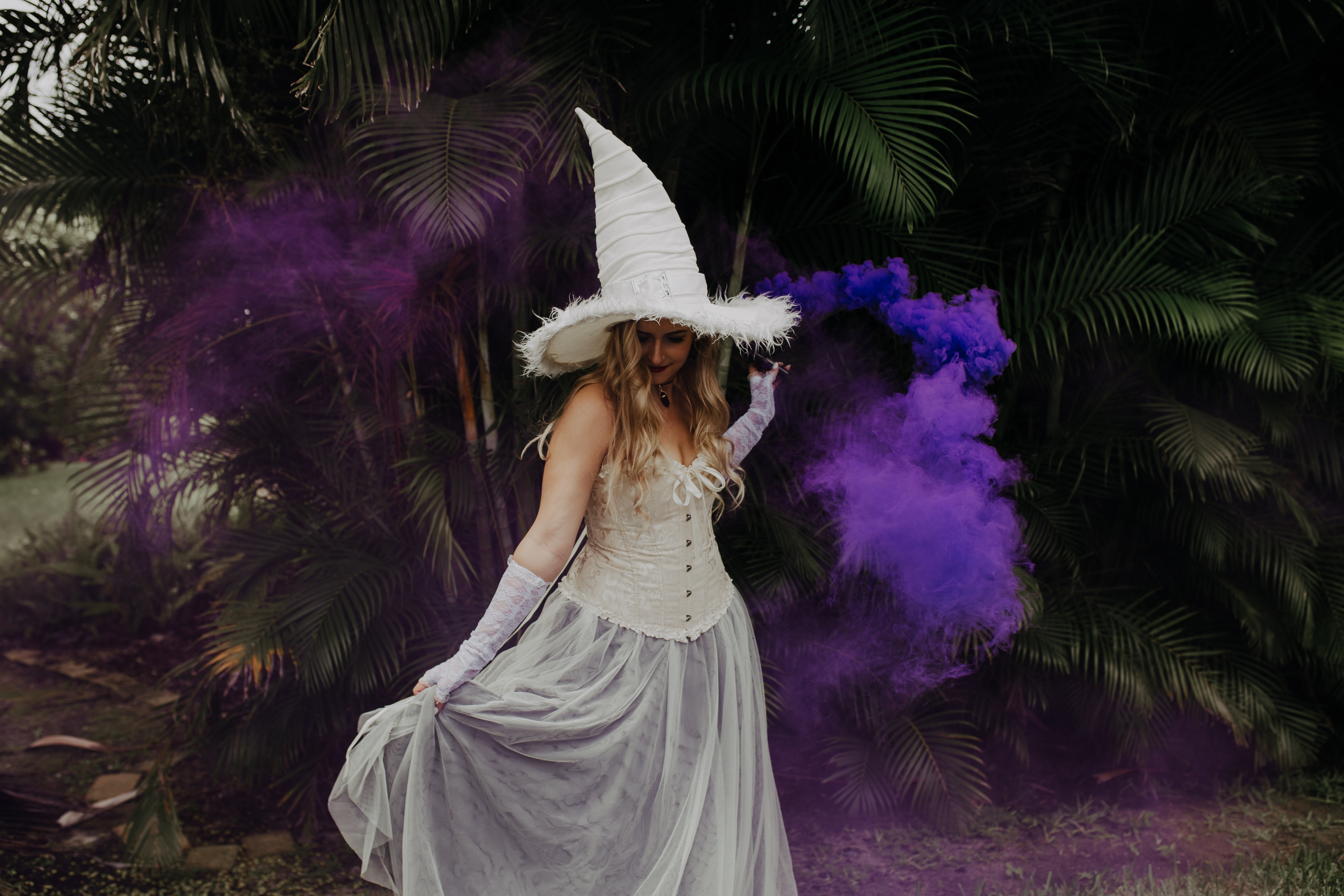 witch bride dances around outside with purple smoke bomb and long flowy tulle dress skirt from revelry