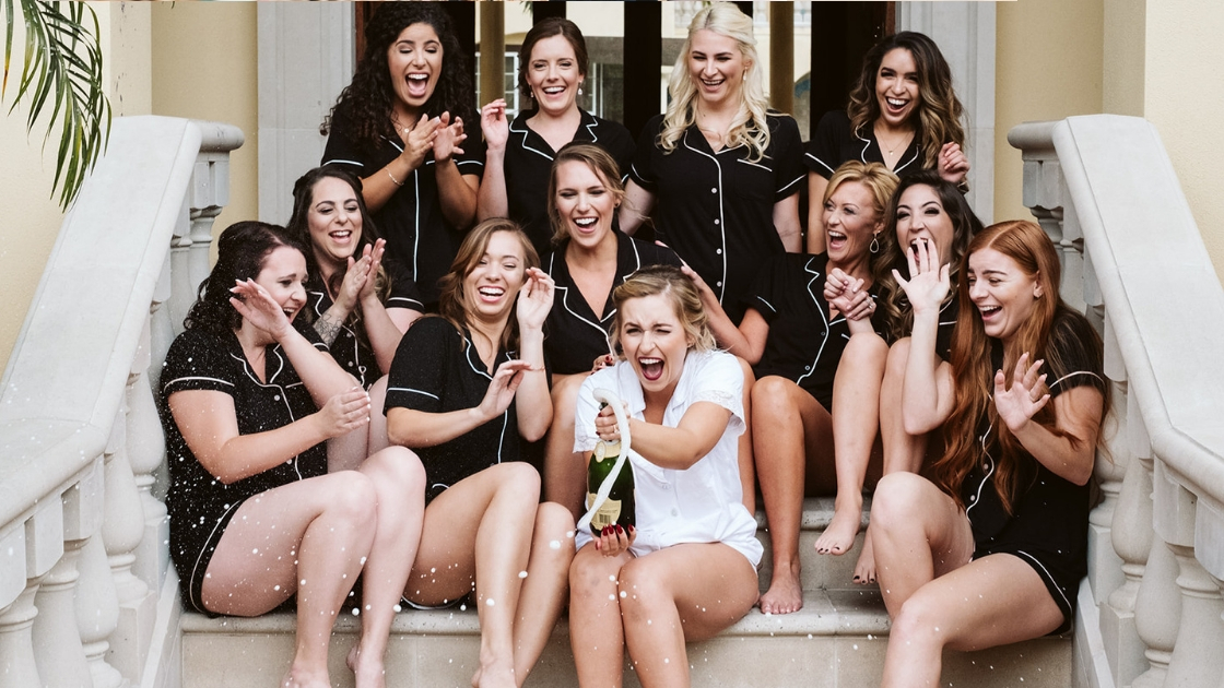 Rachel Varina and 11 person bridal party black and white pajamas champagne photos laughter