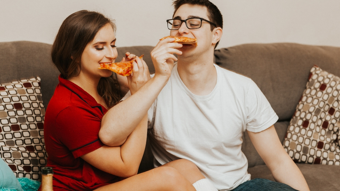 Rachel Varina and husband fiance cuddle on couch and eat pizza planning italian honeymoon