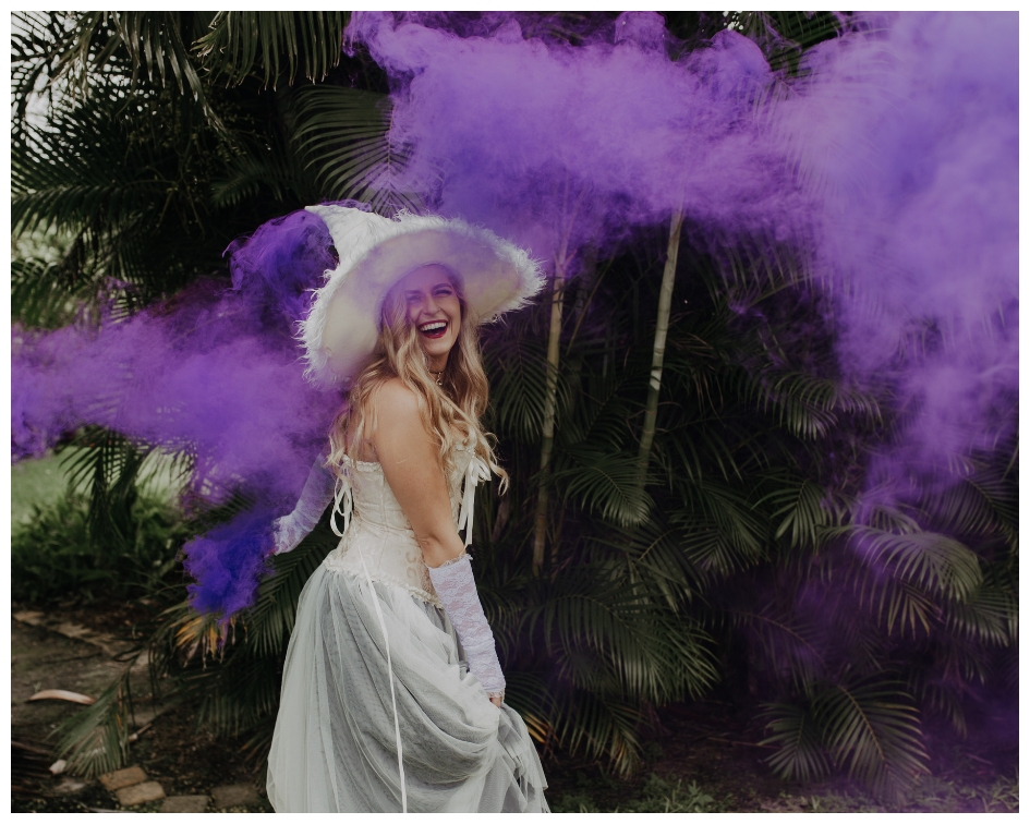 Blonde bride dressed as a witch in all white with a hat corset and tulle skirt laughs in purple smoke