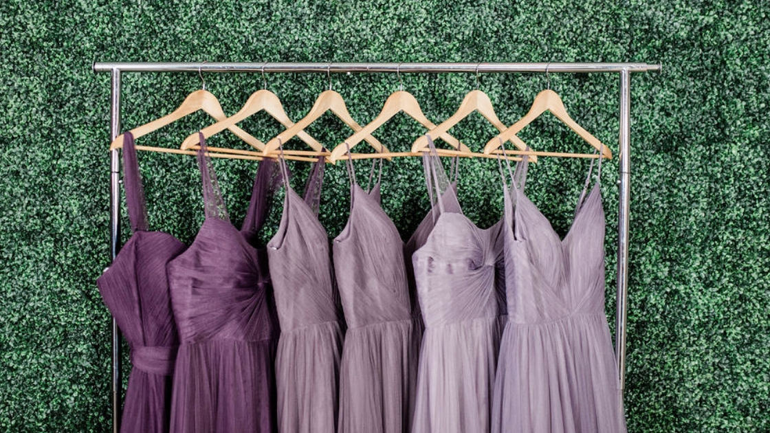 Rack shot tulle bridesmaid dresses purple gowns dark purple wisteria lilac greenery plan wall