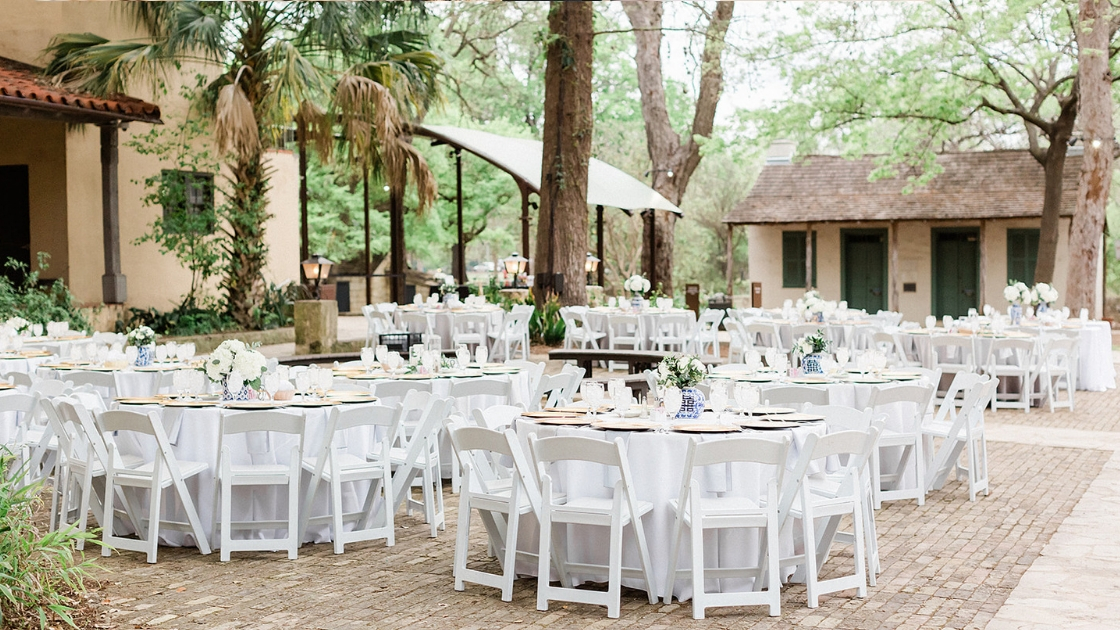 Reception venue white tables and chairs florals and greenery blue vase trees backyard park wedding