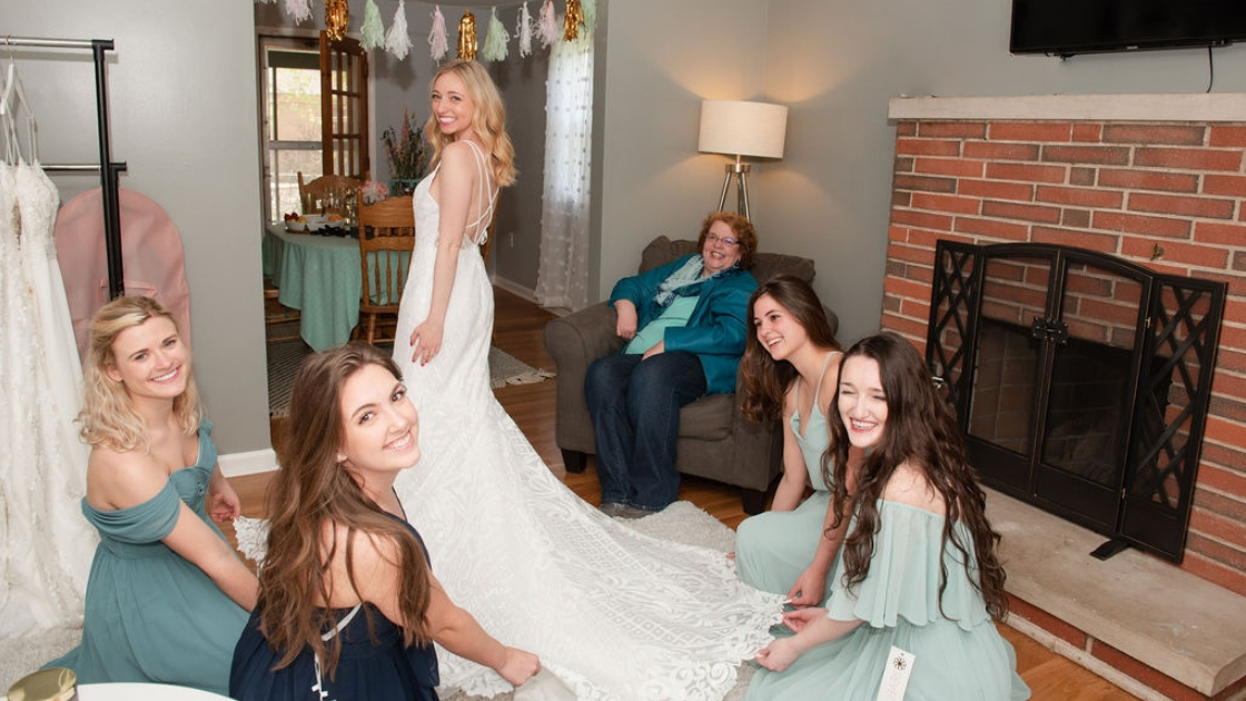 Revelry bride sarah arpino in raden bridal wedding dress gown white dress blue and green chiffon dresses off the shoulder styles mom sitting and watching in the background