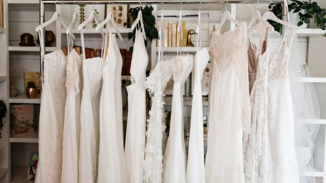 Revelry wedding dresses 11 different styles hanging up on rack at austin revelry try-on party