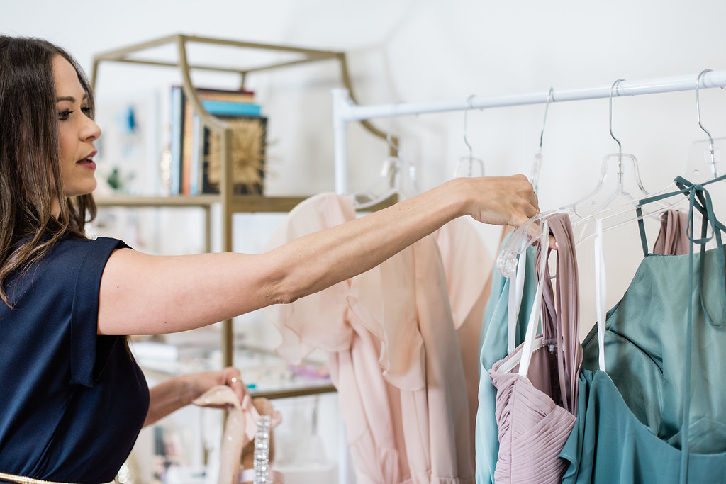 Revelry founder hanging up different dresses in chiffon colors