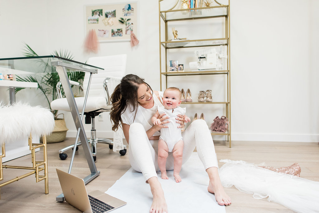 Michelle wearing white yoga attire posing with baby on office floor
