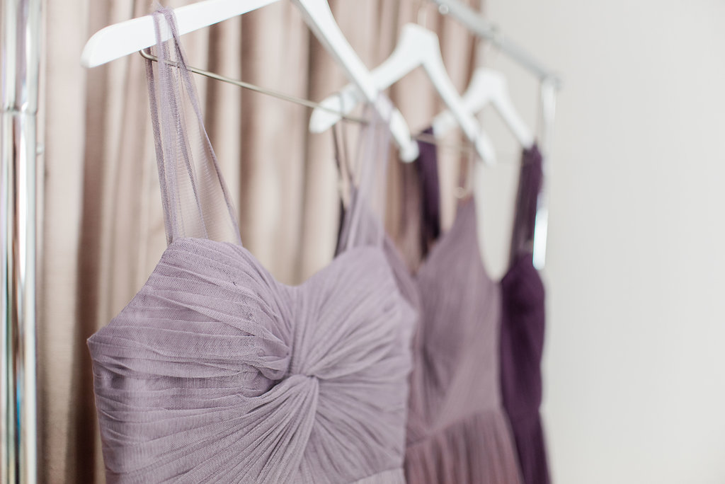 Purple revelry dresses in tulle hanging up on wall with beautiful details
