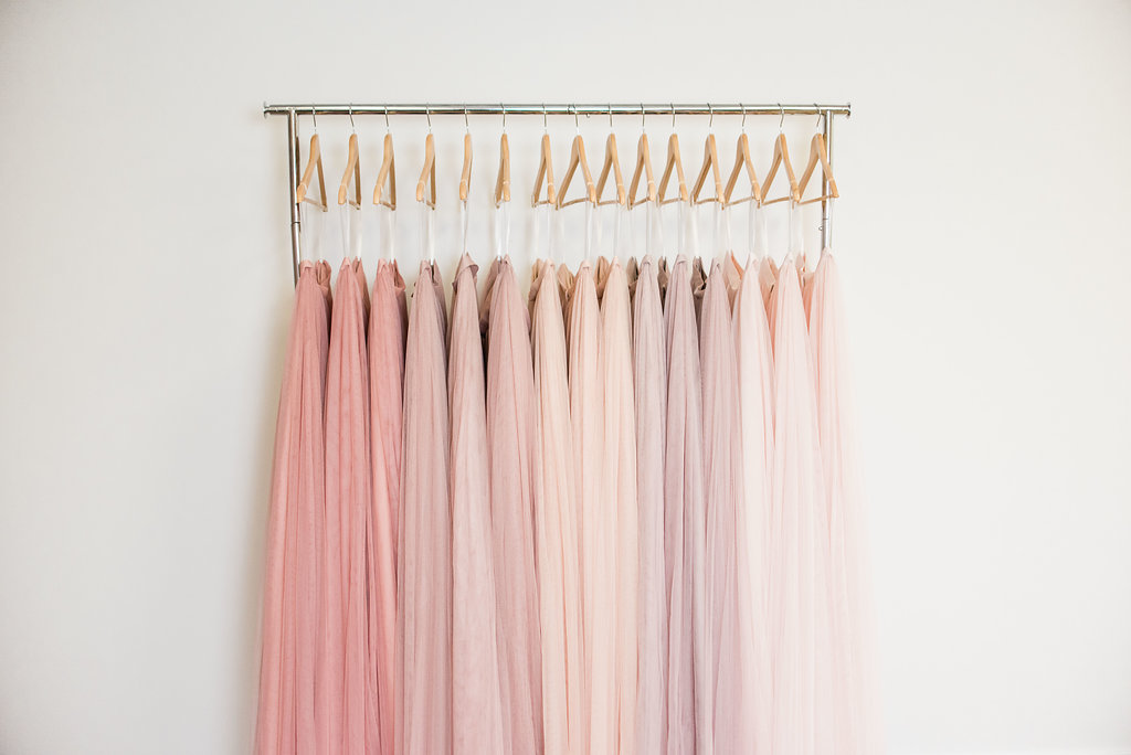 Different shades of blush and pink dresses hanging on wood hangers with white background