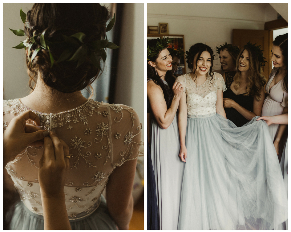 Bride in blue skirt and BHLDN top has her bridesmaids help her get ready on her big day