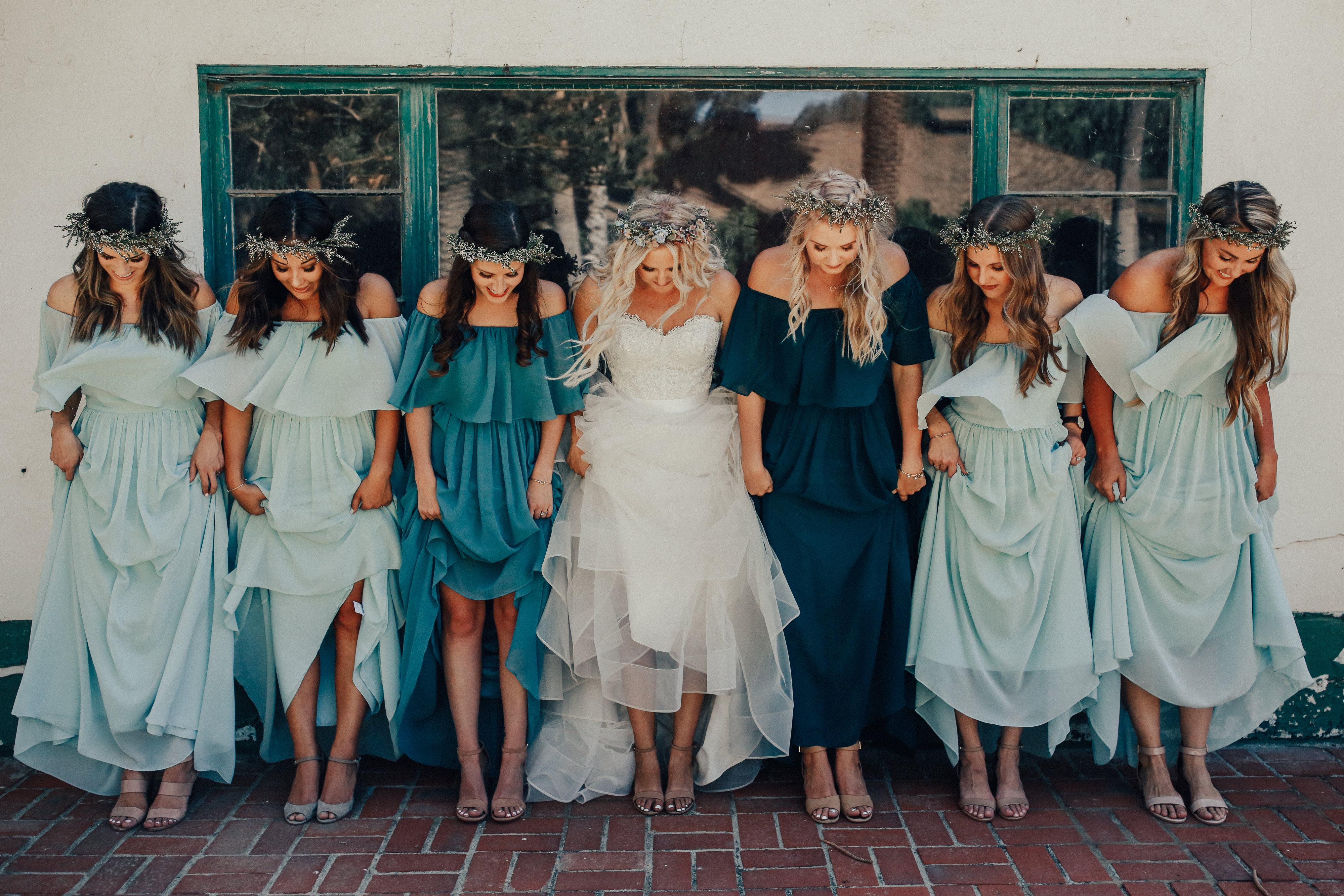 Bride and bridesmaids all in chiffon dresses hold dresses up and look at shoes for pretty boho picture