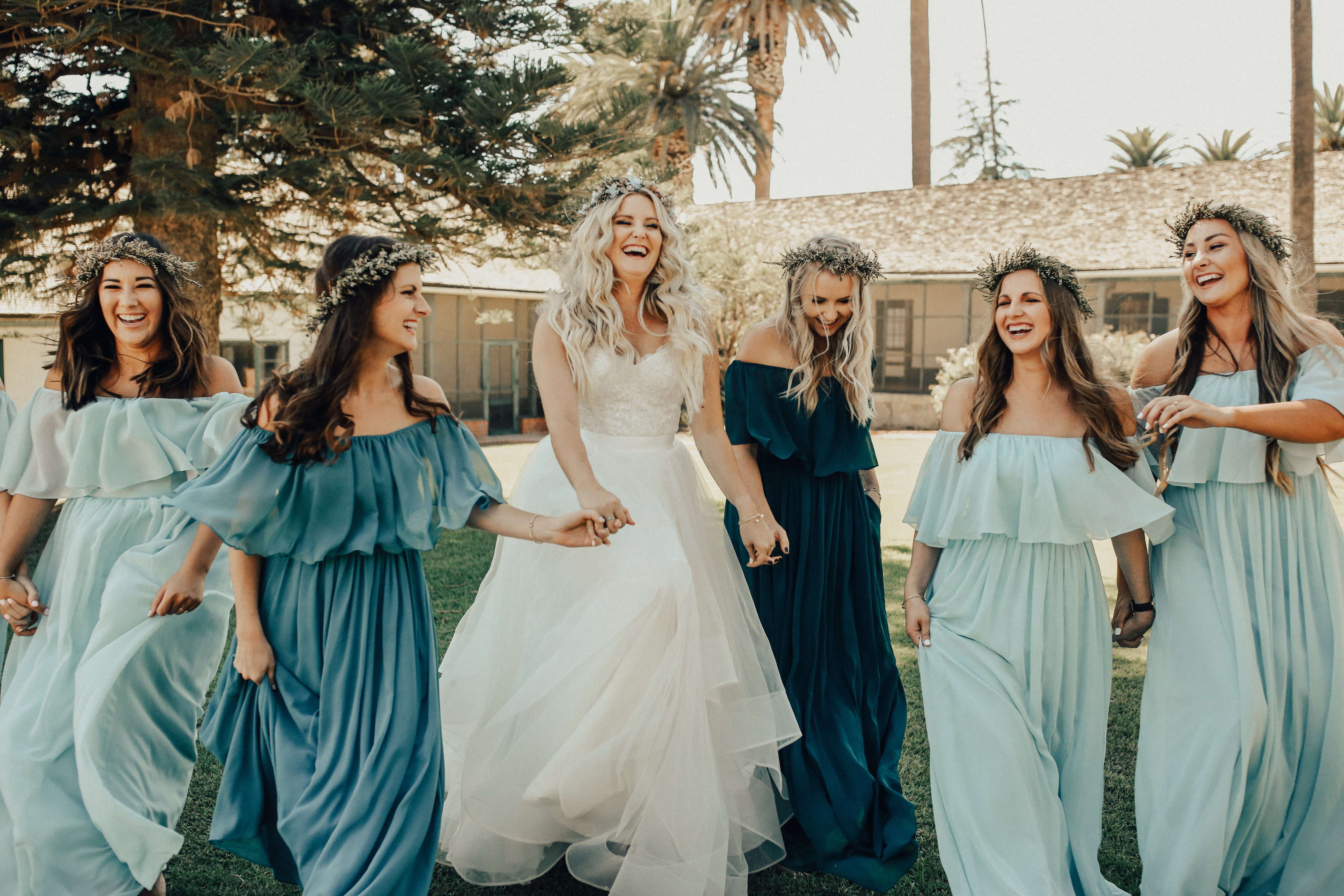 Bridesmaids in blue and green chiffon abigail revelry dresses laugh on wedding day